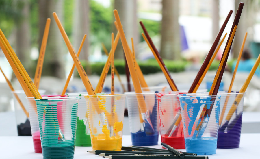 Cups with coloured paint and brushes and pencils