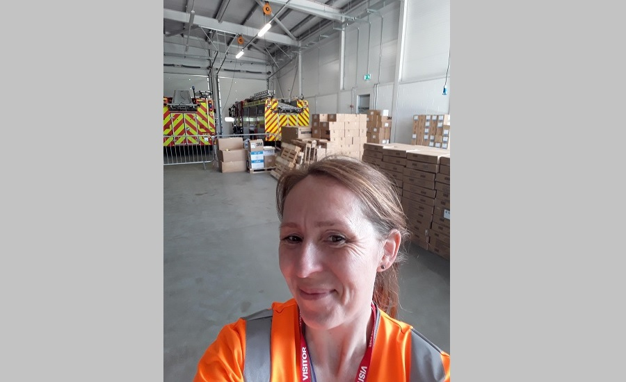 Alice standing in front of boxes of PPE