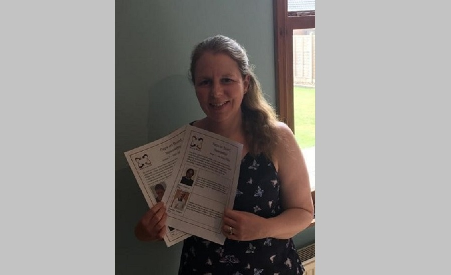 Beth holding the newsletters