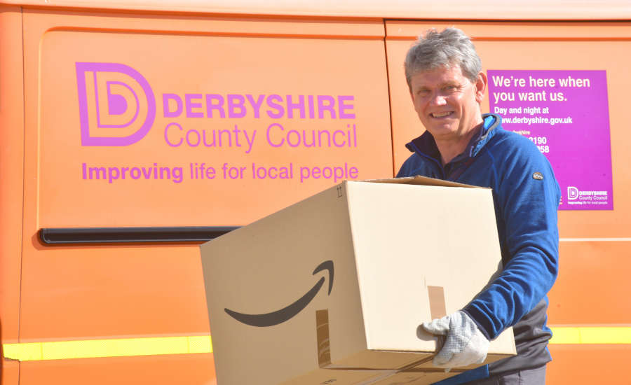 Man holding a box standing in front of a council van