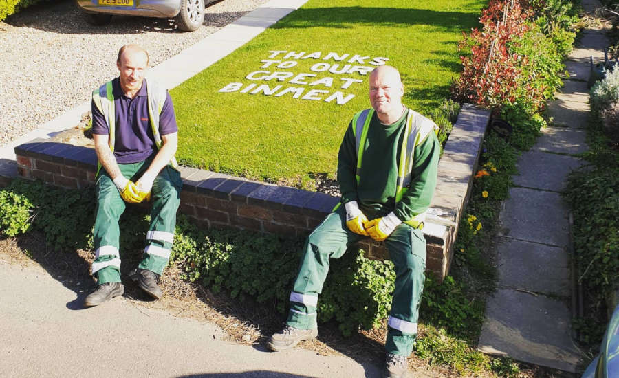 Refuse collectors sitting on a wall with thank you message