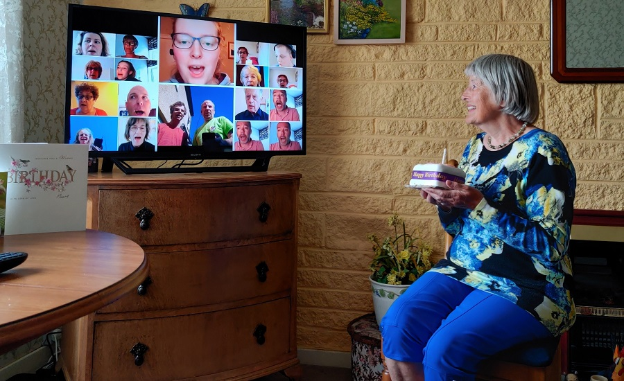 woman holding cake watching conference call on television